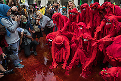 Members of the Extinction Rebellion Red Rebel Brigade take part in a mass civil disobedience involving the spreading of fake blood in Paternoster Square following a Blood Money March through the City of London on 27th August 2021 in London, United Kingdom. Extinction Rebellion were intending to highlight financial institutions funding fossil fuel projects, especially in the Global South, as well as law firms and institutions which facilitate them, whilst calling on the UK government to cease all new fossil fuel investment with immediate effect.