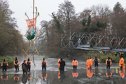 Denham, UK. 8th December, 2020. HS2 security guards form a line across the River Colne in front of Dan Hooper, widely known as Swampy during the 1990s. The climate and roads activist had occupied a bamboo tripod the previous day in order to delay the building of a bridge as part of works for the controversial HS2 high-speed rail link and a large security operation involving officers from at least three police forces, National Eviction Team enforcement agents and HS2 security guards was put in place to facilitate his removal.