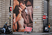 Londoners pass beneath a tall advertising billboard, an ad by menswear retailer Suitsupply, of an intimate kissing couple on Covid 'Freedom Day'. This date is what Prime Minister Boris Johnson's UK government has set as the end of strict Covid pandemic social distancing conditions with the end of mandatory face coverings in shops and public transport, on 19th July 2021, in London, England.