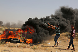 April 13, 2018 - Gaza, Palestinian Territories, Palestine - Palestinians protest near the border fence with Israel, east of Gaza City in the central Gaza Strip. Several thousand Gazans gathered for a third consecutive Friday of mass protests along the border with Israel after violence in which Israeli forces have killed 33 Palestinians and wounded hundreds of others. (Credit Image: © Majdi Fathi/NurPhoto via ZUMA Press)