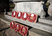 Remembrance poppy wreaths on village war memorial, Snape, Suffolk, England