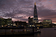 Sunset view towards More London and The Shard at night from the River Thames in London, England, United Kingdom. Taken from a riverboat offering a unique view.
