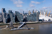 An aerial view from an Emirates Air Line cable car of showing Thames riverside apartment, an Uber Boat and the O2 Arena on the Greenwich Peninsular, on 11th August 2021, in London, England.