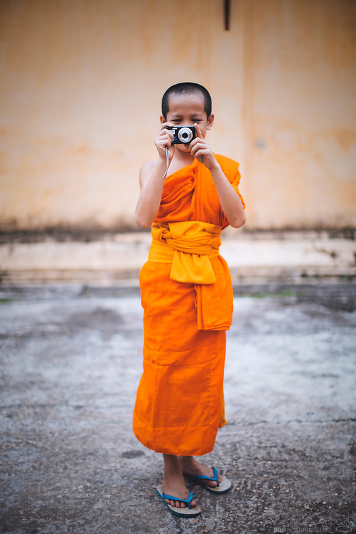 A young Buddhist monk taking a photograph with a digital camera, Wat Si Saket, Vientiane, Laos