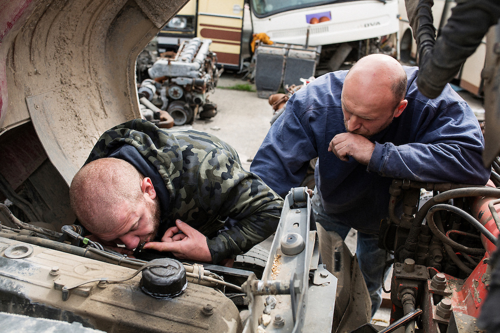 Dinko Valev's junkyard in Yambol, Bulgaria. Valev tries to get the fuel system to work on a truck by sucking fuel through a blocked fuel line.<br /> <br /> Matt Lutton / Boreal Collective for VICE