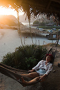 A woman relaxes in a hammock at sunset in Maruata, Michoacan State, Mexico. Maruata is a Pomaro fishing village set in a beautiful bay and a popular destination among independent-minded travelers.