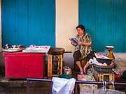 26 FEBRUARY 2016 - BANGKOK, THAILAND: A fish monger set up in front of an abandoned shophouse in Verng Nakorn Kasem neighborhood. Verng Nakorn Kasem, also known as the Thieves' Market, was one of Bangkok's most famous shopping districts. It is located on the north edge of Bangkok's Chinatown district, it grew into Bangkok's district for buying and selling musical instruments. The family that owned the land recently sold it and the new owners want to redevelop the famous area and turn it into a shopping mall. The new owners have started evicting existing lease holders and many of the shops have closed. The remaining shops expect to be evicted by the end of 2016.      PHOTO BY JACK KURTZ