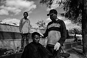 Para sobrevivir, algunos migrantes han comenzado a realizar actividades como peloqueria, cobran mas barato que en la ciudad y asi obtienen algo de ingresos para sobrevivir mientras esperan cruzar a los Estados Unidos. Fotografo César Rodríguez.