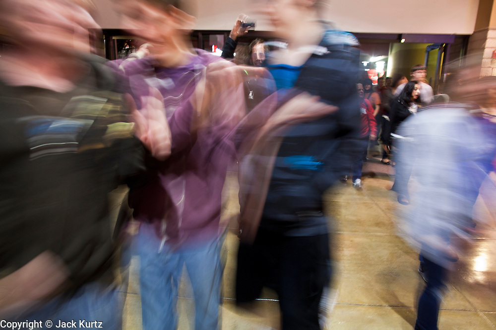 """24 NOVEMBER 2011 - PHOENIX, AZ:  People run into Paradise Valley Mall Thursday. The mall opened its doors a couple of minutes before the scheduled midnight opening.  """"Black Friday,"""" the unofficial start of the holiday shopping season started even earlier than normal. Many stores, including Target and Best Buy, opened at midnight.    Photo by Jack Kurtz"""