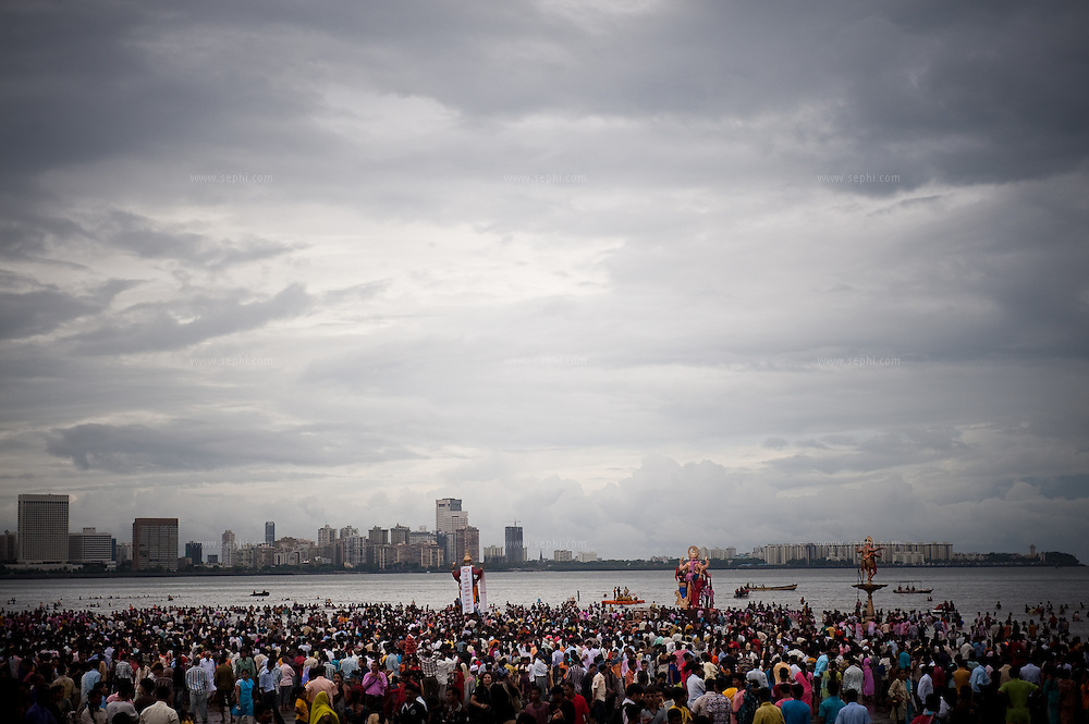The skyline of the city of Mumbai on a cloudy day are the backdrop for huge decorated  idols iof lord Ganesh taken for immersion in the Indian ocean on the last day of the Ganesh Chaturthi festival. Ganesh, the elephant-headed son of Shiva and Parvati is widely worshiped as the supreme God of wisdom, prosperity and good fortune. Mumbai, September 2009.
