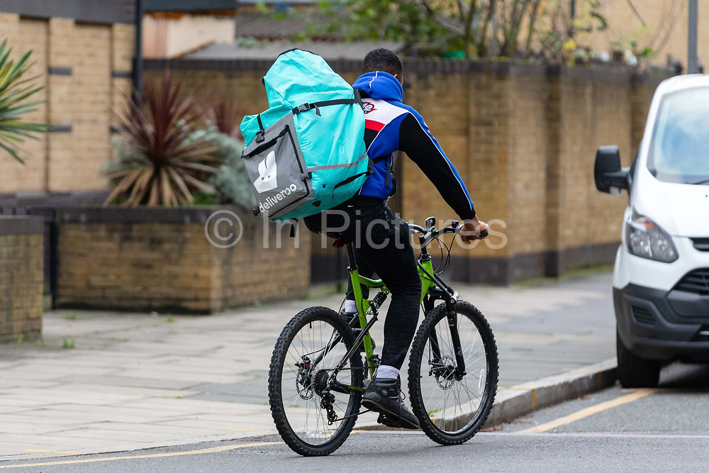 A Deliveroo cycle courier with a large backpack delivering in London, England on December 21, 2018.