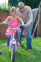 Little girl playing on bike in the garden with her father,