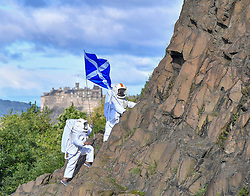 Pictured: Joy Maria Onotu and Sarah Miele hoist the flag on the crags with Edinburgh Castle in the background.<br /> <br /> Stars of the Fringe show 'Valentina's Galaxy' appeared as astronauts on iconic Salisbury Crags in Edinburgh in preparation for their show at this year's Edinburgh Fringe.<br /> <br /> © Dave Johnston / EEm