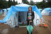 """Onagawa  - Satsuki KASHIMURA - Village de tentes -Juin 2011<br /> Satsuki KASHIMURA devant sa tente. """"Nos journées se passent dans l'attente. Nous n'avons rien à faire ici, nous navons plus de travail. Il n'y a plus de ville. De temps en temps on fait la sieste ou comme aujourd'hui où la pluie produit beaucoup de boue, nous nettoyons nos entrés et les sanitaires extérieurs."""""""