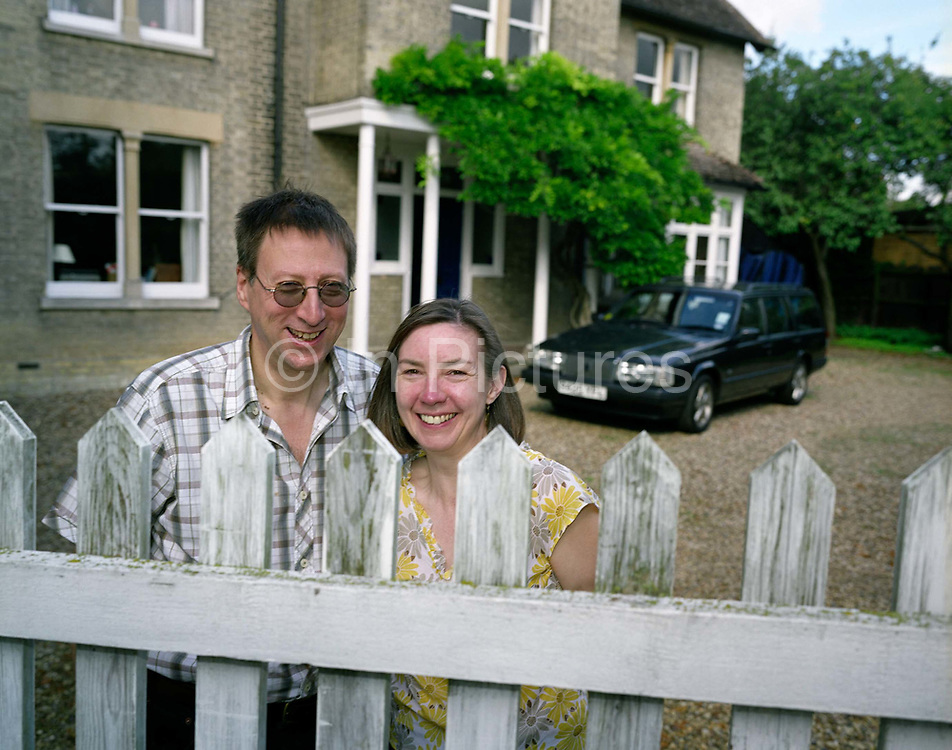 Ordinary husband and wife Mark and Christine Easterfield stand awkwardly at the dirty picket fence with their Volvo car parked on the gravel drive outside their home near Cambridge, England. They are among the thousands of people who have paid the $200,000 fee for a seat on Richard Branson's Virgin Galactic space flights. Aboard the re-usable space vehicle will be 6 passengers, each of whom will have paid $200,000 for the 40 minute flight to 360,000 feet (109.73km, or 68.18 miles) and to experience just 6 minutes of weighlessness. Flights start around 2009/10 from a Mojave desert test facility but therafter, at the new Philippe Starck-designed SpacePort America, New Mexico, USA. a 27 square mile, $225 million headquarters and mission control facility near Las Cruces.