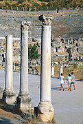 "Visitors walk beneath Corinthian order columns at the Great Theatre of Ephesus, in the Republic of Turkey. Published in the travel handbook ""Moon Istanbul & the Turkish Coast"" by Jessica Tamtürk, Avalon Travel Publishing, 2010. The Great Theatre of Ephesus, the largest outdoor theatre in the ancient world, was begun during Hellenistic times (probably during the reign of Lysimachos in the third century BC), and was altered and enlarged from 41-117 AD by Roman emperors Claudius, Nero, and Trajan. The Greek builders dug out a space from Mount Pion (present-day Panayir Dagi) to fit the 30-meter (100-foot) high theater, which accommodated 25,000 people, or 10 percent of the population of Roman Ephesus at its peak. The theatre exhibited the fights of wild beasts and of men with beasts. In the 1st century AD, the Apostle Paul delivered a sermon condemning pagan worship in this theater. Subsequently, followers of the Ephesian cult of Artemis forced Paul and his followers out. Over several centuries, the Cayster River filled the harbor of Ephesus with silt, creating a malaria-infested swamp, pushing the sea 4 kilometers away and cutting off the city's commerce and wealth. By the 6th century AD, Emperor Justinian decided to build the Saint John Basilica 3 kilometers away, which effectively moved the city center to Selçuk."