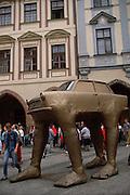 Gold painted sculpture of a Trabant (E. German made car) with legs. Prague, Czech Republic.