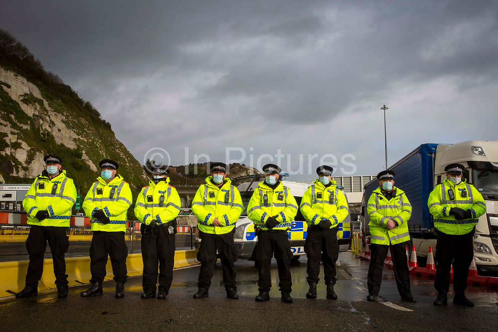 The Police line as tensions are high between police and drivers who have been waiting over 48 hours for the Port of Dover to re-open, on the 23rd of December 2020, Dover, Kent, United Kingdom. The French border was closed due to a new strain of COVID-19 all travellers are now waiting to receive a COVID-19 test before they can board a ferry to Calais, France. Dover is the nearest port to France with just 34 kilometres 21 miles between them. It is one of the busiest ports in the world. As well as freight container ships it is also the main port for P&O and DFDS Seaways ferries.