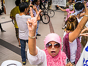 """02 JUNE 2013 - BANGKOK, THAILAND:  An Muslim anti-government protester wearing a carnival mask during a protest in Bangkok. The so called White Mask protesters are strong supporters of the Thai monarchy. About 300 people wearing the Guy Fawkes mask popularized by the movie """"V for Vendetta"""" and Anonymous, the hackers' group, marched through central Bangkok Sunday demanding the resignation of Prime Minister Yingluck Shinawatra. They claim that Yingluck is acting as a puppet for her brother, former Prime Minister Thaksin Shinawatra, who was deposed by a military coup in 2006 and now lives in exile in Dubai.    PHOTO BY JACK KURTZ"""