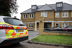 © London News Pictures. 21/05/2016. Weybridge, UK. A Police car and a police cordon outside a property on the St George's Hill estate in Weybridge, Surrey where the body of a woman in her 30's was discovered by paramedics this morning (Sat). Photo credit: Peter Macdiarmid/LNP