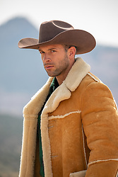 Portrait of a rugged good looking cowboy in a sheepskin coat