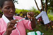 Nurse Agnes from Bwindi Community Hospital prepares a vaccination during the out reach clinic in Kitahurira, the only Batwa tribe settlement in Mpungu district.  She administers Polio and measles vaccinations to newborn children in the community. The Mpungu district is on the edge of the Bwindi Impenetrable Forest, Western Uganda.