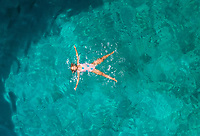 Aerial view of a attractive young woman in swimsuit floating in the sea off Atokos island, Greece