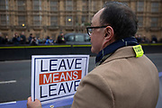 Vote Leave protester has a Bollocks to Brexit sticker placed on his coat collar by a mischievous Anti Brexit pro Europe demonstrator, resulting in a mixed message in Westminster on the day of the 'meaningful vote' when MPs will back or reject the Prime Minister's Brexit Withdrawal Agreement on 15th January 2019 in London, England, United Kingdom.