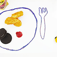 Kids meal , chicken nuggets ,cookies , dipping sauce and fruit smoothie on white .