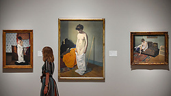 """© Licensed to London News Pictures. 27/06/2019. LONDON, UK.  A staff member passes (C) """"Nude Holding Her Gown (Femme nue retenant sa chemise à deux mains"""", 1904, by Félix Vallotton. Preview of """"Félix Vallotton:  Painter of Disquiet"""", an exhibition of paintings and prints Swiss artist Félix Vallotton at the Royal Academy of Arts.  Around 100 works are on show 30 June to 29 September 2019.   Photo credit: Stephen Chung/LNP"""