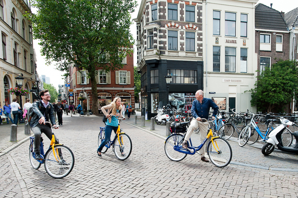 In Utrecht staan die mensen met een OV-fiets in de binnenstad.<br /> <br /> In Utrecht, three people are standing in the city center with a rental bike.