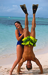woman laughing while holding a man who is doing a handstand at the beach