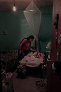 """Maricel (30) acaricia la cabeza de su hijita Renata (3) en la habitación que adecuaron para ella. Renata fue diagnosticada con Tay Sachs a partir de su primer año de vida. Esta severa enfermedad es Neurodegenerativa y compromete a todo el sistema nervioso central. Desde que recibió el diagnóstico de su hija, Maricel ya no duerme más de noche. """"Hace tres años que sólo duermo una hora por noche. No sé cómo sigo de pie todavía. Es muy difícil cuando faltan los medicamentos y la obra social no cumple. De eso depende que nuestros hijos pasen la noche."""" -Dice Maricel-"""