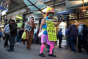 Man advertising for Salsa Dancing classes using a sandwich board and amusing costume outside Whitechapel Station in East London, UK. Dance lessons and dancing in general is on the increase in the UK following the popularity of TV dance shows.