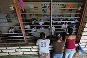 Parents look at their children throught the window as class is conducted at the Escuela Republia del Mexico school in Guaimaca, Honduras.  Over 94% of Honduran children are enrolled in school, yet only 40% actually complete their schooling.  Hounduras is considered the third poorest country in the Western Hemisphere (Haiti, Nicaragua). With over 50% of the population living below the poverty line and 28% unemployed, Hondurans frequently turn to illegal immigration as a solution to their desperate situation. The Department of Homeland Security has noted an 95% increase in illegal immigrants coming from Honduras between 2000 and 2009, the largest increase of any country.