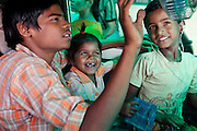 Sachin, 18, (left) Meenakshi,7, and another disable child are sitting in the Chingari bus ready to go home after a day spent at the local NGO, caring for disabled  children in Bhopal, Madhya Pradesh, India, near the abandoned Union Carbide (now DOW Chemical) industrial complex.