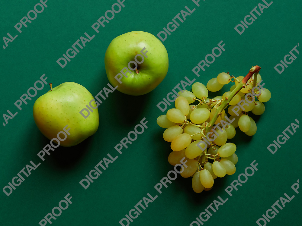 Above view of isolated set of a green apple with a bunch of sweet seedless grapes in studio with green background
