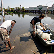 NEW ORLEANS, LA - September 4, 2005:  Two men who said they were neighbors reach dry land for the first time on Sept, 4, 2005 after evacuating by small boat following the destruction caused by Hurricane Katrina. (Photo by Todd Bigelow/Aurora)