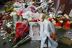 © Licensed to London News Pictures. 12/01/2016. London, UK. A newspaper displaying an image of David Bowie sits amongst other tributes in Brixton where he was born. Photo credit: Peter Macdiarmid/LNP