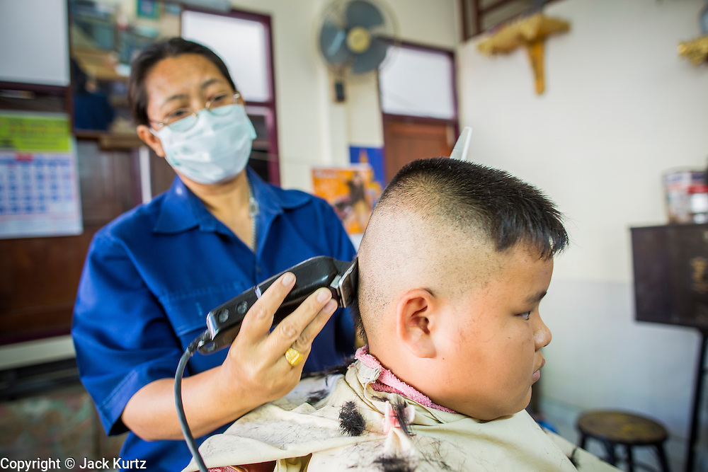 13 JANUARY 2013 - BANGKOK, THAILAND:A barber gives a boy haircut in her barbershop, which is also the living room of her home, in the Bang Luang neighborhood in Bangkok. The Bang Luang neighborhood lines Khlong (Canal) Bang Luang in the Thonburi section of Bangkok on the west side of Chao Phraya River. It was established in the late 18th Century by King Taksin the Great after the Burmese sacked the Siamese capital of Ayutthaya. The neighborhood, like most of Thonburi, is relatively undeveloped and still criss crossed by the canals which once made Bangkok famous. It's now a popular day trip from central Bangkok and offers a glimpse into what the city used to be like.     PHOTO BY JACK KURTZ