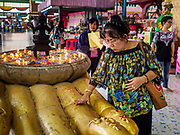 """30 DECEMBER 2017 - BANG KRUAI, NONTHABURI, THAILAND:  A woman prays to make merit for the new year at Wat Ta Khien, about 45 minutes from Bangkok in Nonthaburi province. The temple is famous for the """"floating market"""" on the canal that runs past the temple and for the """"resurrection ceremonies"""" conducted by monks at the temple.      PHOTO BY JACK KURTZ"""