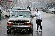 23 NOVEMBER 2020 - DES MOINES, IOWA: A volunteer checks in people picking food packages before a Thanksgiving food distribution at a park in Des Moines during a snowstorm. The food distribution was organized by Urban Dreams, a community empowerment NGO in central Des Moines, and the NAACP. The food was provided by Hy-Vee, a regional grocery store chain based in Des Moines. They had about 450 meals available. A spokesperson for Hy-Vee said the company was giving away more than 20,000 Thanksgiving meals this year. The Food Bank of Iowa said food insecurity in Des Moines has doubled since the start of the Coronavirus pandemic.   PHOTO BY JACK KURTZ
