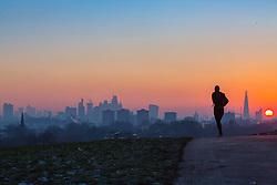 London, December 12 2017. A jogger's silhouette is seen against the skyline as the sun rises on a clear very cold morning in London, seen from Primrose Hill in Camden. © Paul Davey
