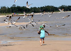 09 May 2010. Waveland, Mississippi USA. <br /> A child enjoys a wonderful day at the beach, possibly one of the last for many years to come. Locals, tourists and visitors relax and enjoy the beauty of South Beach,  an hour from New Orleans. Just a few miles off the coast, an impending disaster looms. With the continual flood of oil washing into the Gulf of Mexico and as winds turn and begin to push from the south, it is only and matter of when, not if the oil reaches the beaches. The barrier islands offshore are taking a battering soaking up the initial fronts of oil threatening everything in it's ever encroaching path. <br /> Photo; Charlie Varley/varleypix.com