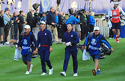 Team Europe's Thorbjorn Olesen (second left) and Rory McIlroy (centre right) walk down the first fairway during the Fourballs match on day one of the Ryder Cup at Le Golf National, Saint-Quentin-en-Yvelines, Paris.