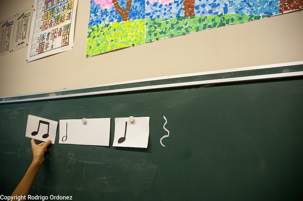 The teacher lays musical notes on the blackboard during a music class at Hakusan Primary School in Kamaishi, Japan.