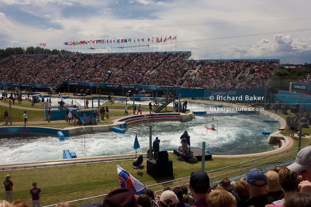 Wide view of the canoe slalom at the Lee Valley White Water Centre, north east London, on day 3 of the London 2012 Olympic Games. The Lee Valley White Water Centre is located 30 kilometres north of the Olympic Park, on the edge of the 1,000-acre River Lee Country Park - part of the Lee Valley Regional Park. The centre has two separate courses: a 300 metre Olympic-standard competition course with a 5.5m descent, and a 160m intermediate/training course with a 1.6m descent. Whitewater course specialists Whitewater Parks International, working with civil and structural engineers Cundall, are the designers of the whitewater courses.