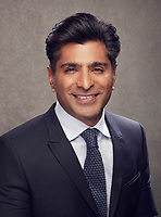 Corporate Headshot textured grey background fully styled and colour graded featuring asian business man in blue suit