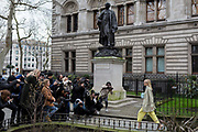 As if posing on an outdoor catwalk, a young fashionista woman walks towards cameras gathered outside the The National Portrait Gallery where a statue to the actory Henry Irving 1838-1905 looks down on the frenzied procedings, during London Fashion Week, on 17th February 2020, in London, England.