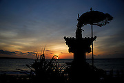 Small shrine and symbolic umbrella silhouetted against setting sun, Jimbaran Bay, Bali, Indonesia. Jimbaran Bay was the location of the second Bali terrorist bombing on October 2, 2005.